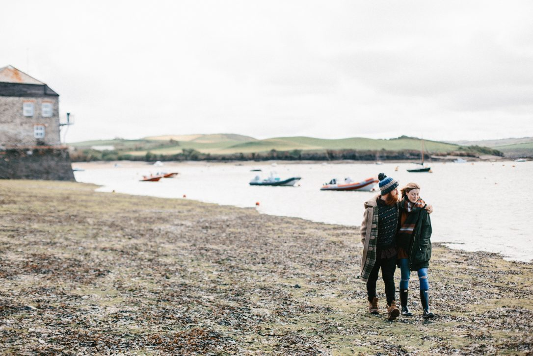 Couple walking along Rock beach, North Cornwall