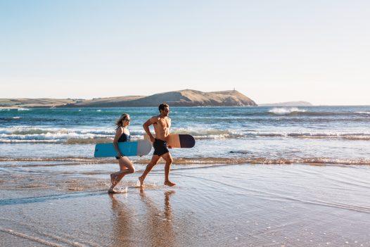 Bellyboarders on Polzeath beach, North Cornwall