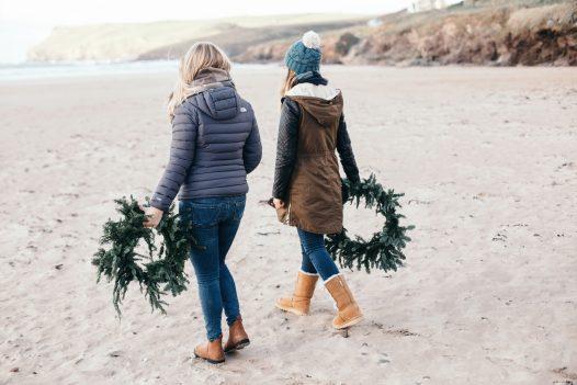 The Latitude50 team with fir Christmas wreaths on Polzeath beach