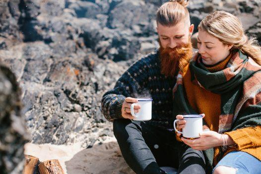 Couple with mugs of hot chocolate on Rock beach