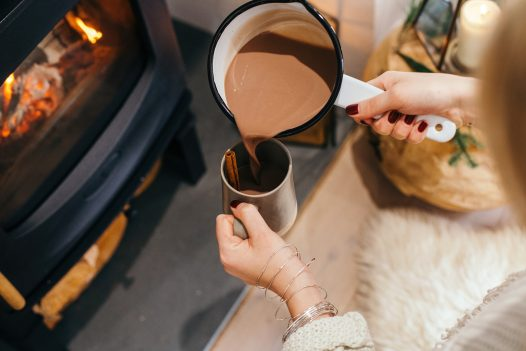 Pouring a cup of cocoa by the fire