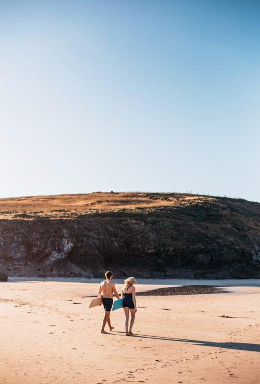 Couple bellyboarding at Baby Bay, Polzeath