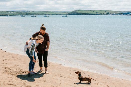Couple walking dog on Rock beach