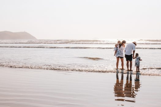 Family splashes in the sea at Polzeath, North Cornwall