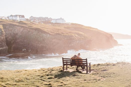 Couple watching the sun set at Port Gaverne, North Cornwall
