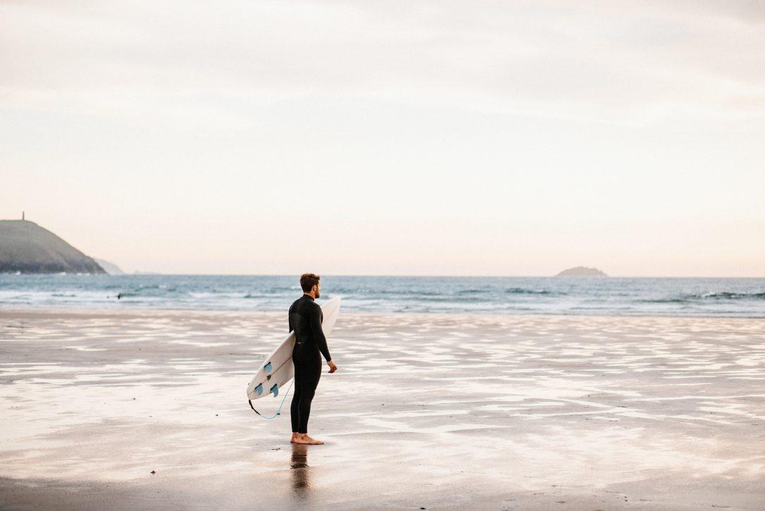 Surfer on Polzeath beach, North Cornwall
