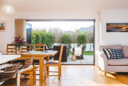 Dining area and view to garden at Clifden, a self-catering holiday house in New Polzeath, North Cornwall