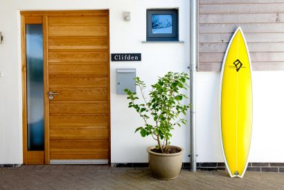 Front door and surf board at Clifden, a self-catering holiday cottage in New Polzeath, North Cornwall